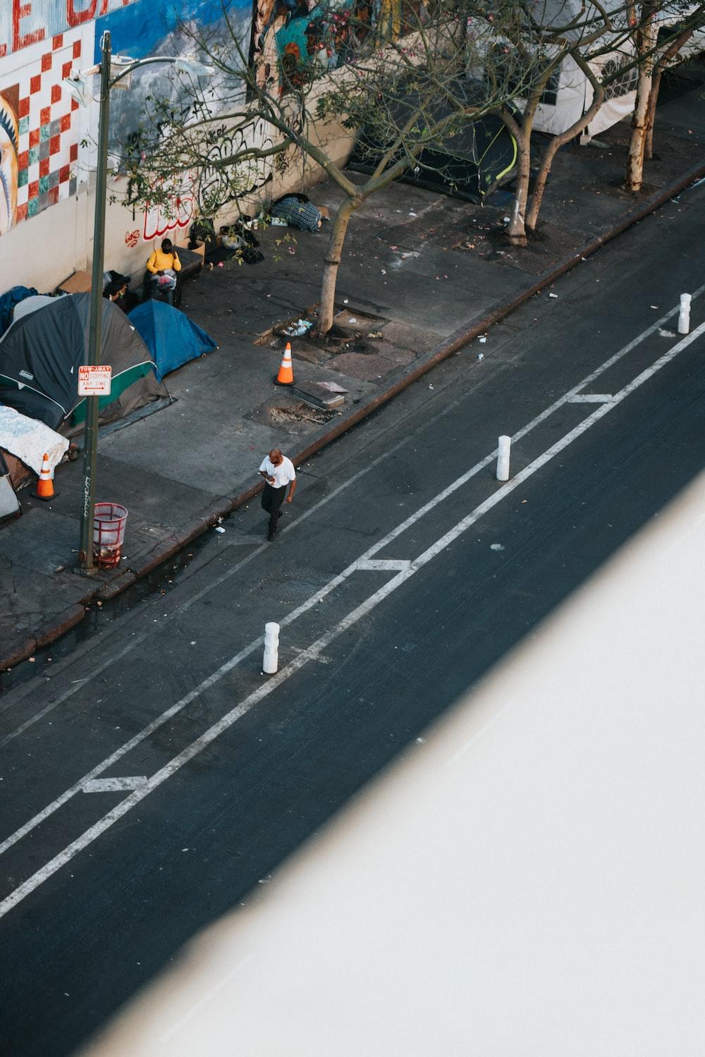 woman in white shirt walking on sidewalk during daytime