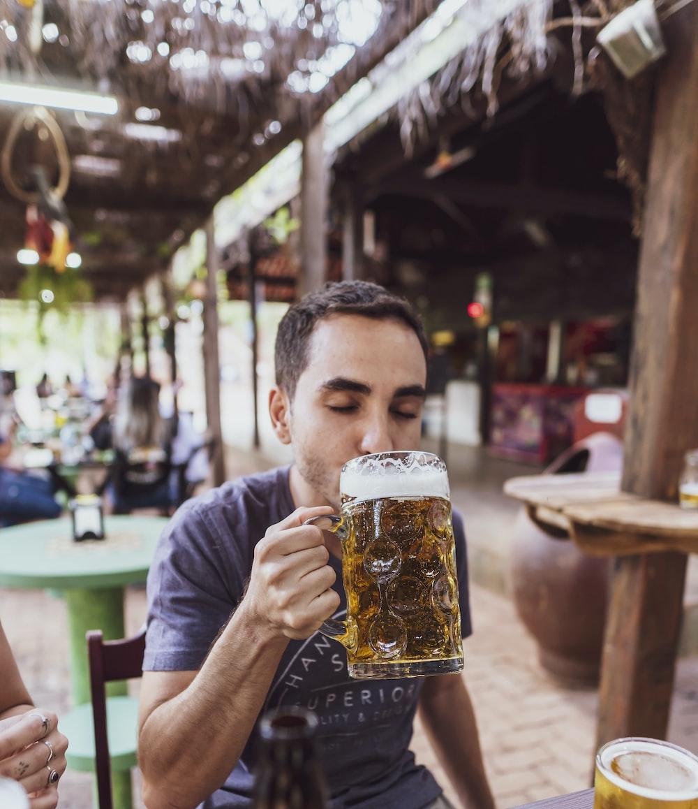 man in gray crew neck t-shirt drinking beer