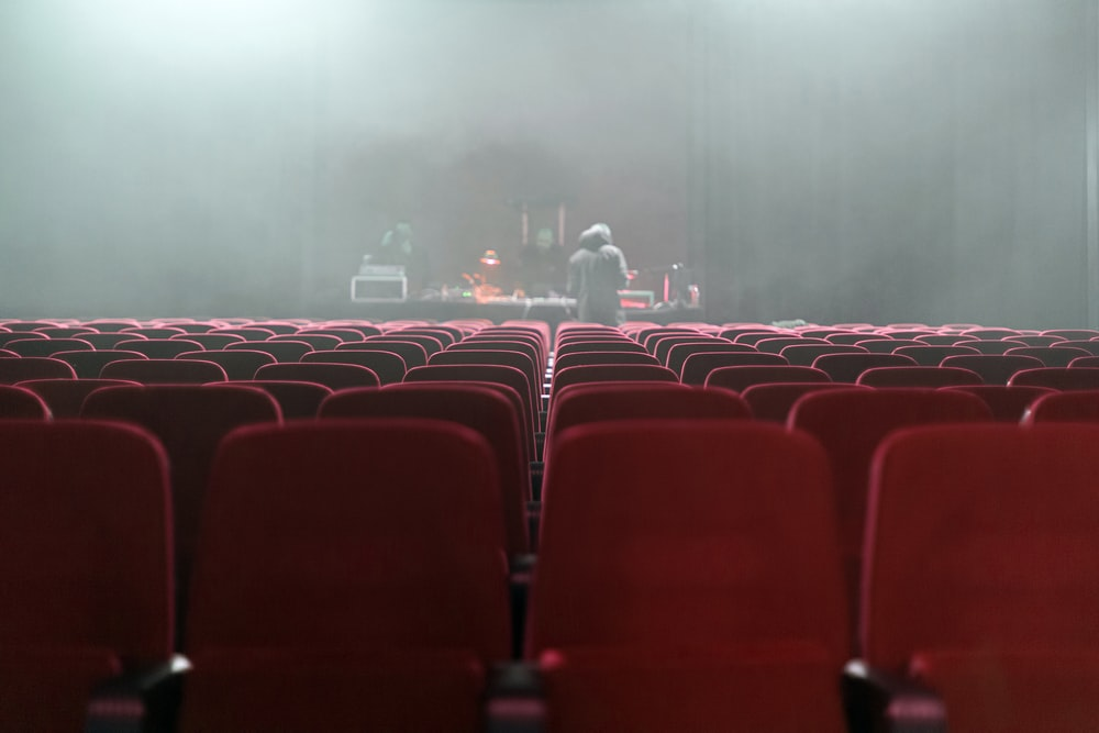 people sitting on red chairs watching a band performing on stage