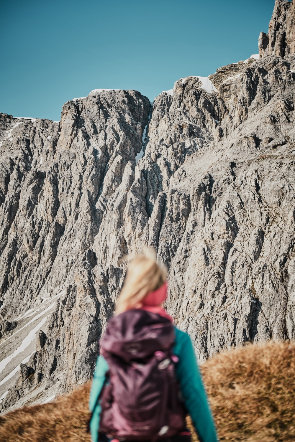 woman in purple jacket standing near rocky mountain during daytime
