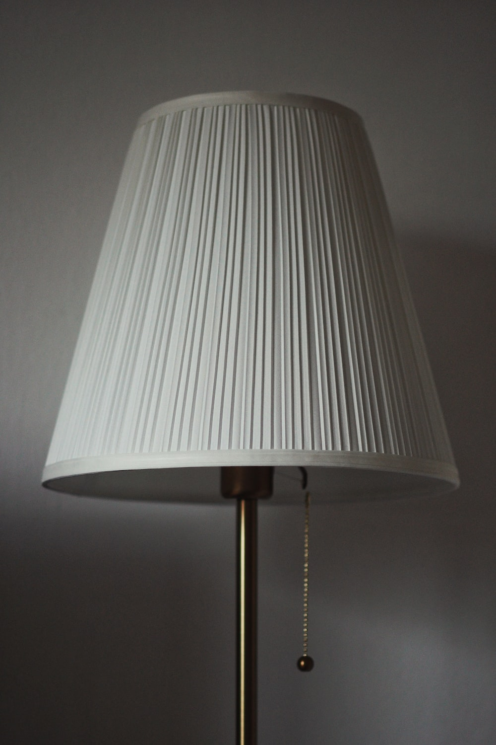 white table lamp turned on near white wall