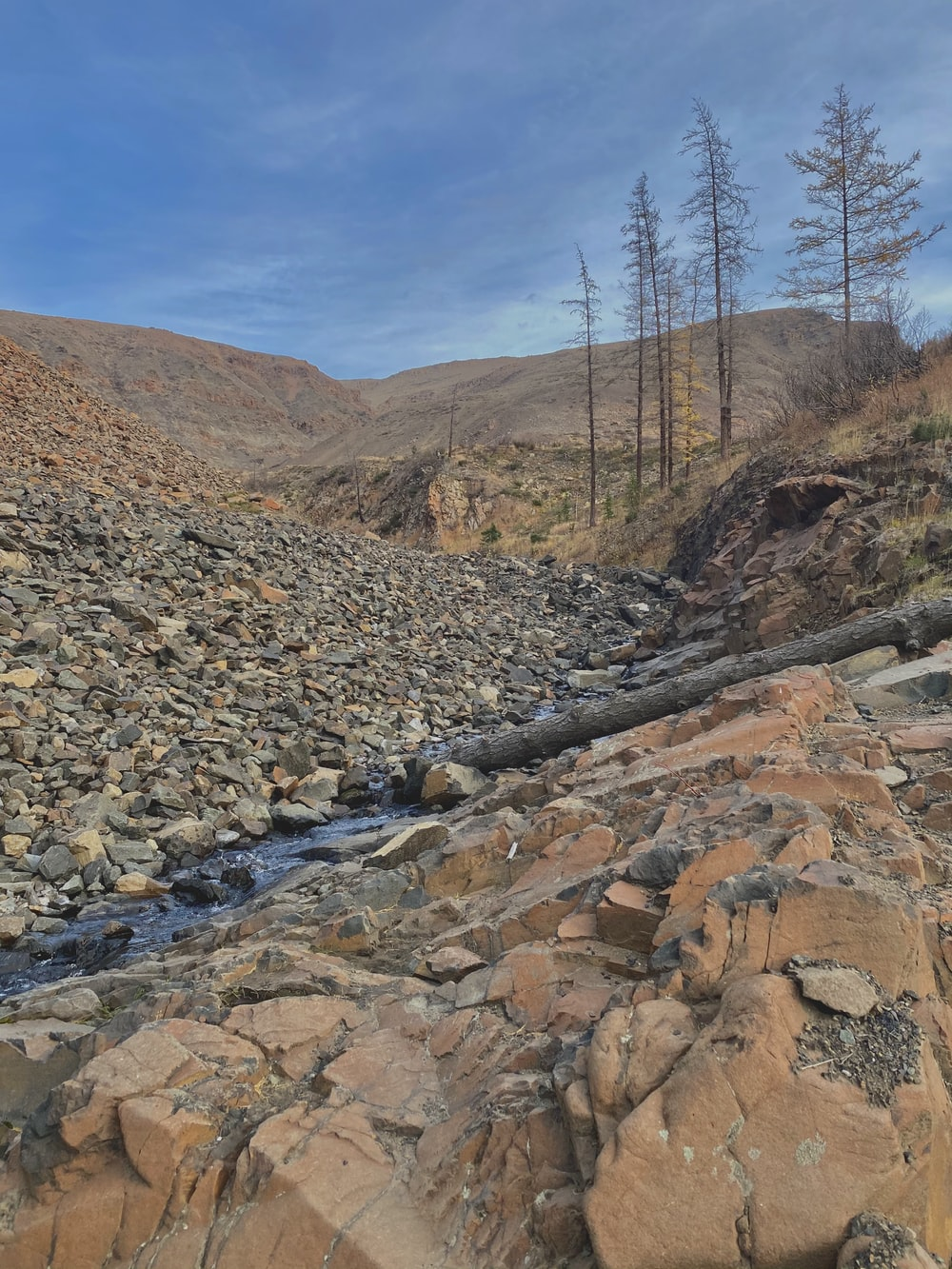 rocky river between brown mountains under blue sky during daytime