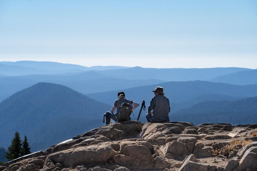 3 men sitting on brown rock formation during daytime