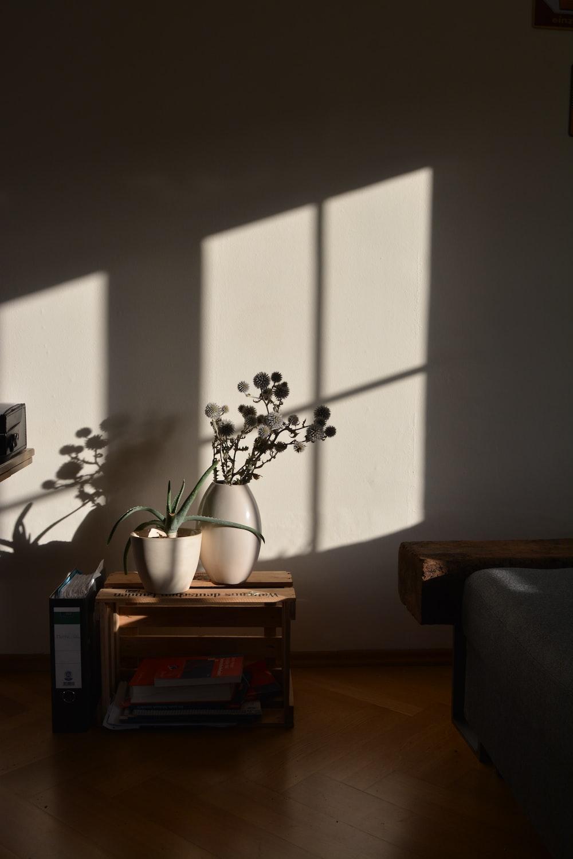 white flower in white ceramic vase on brown wooden table