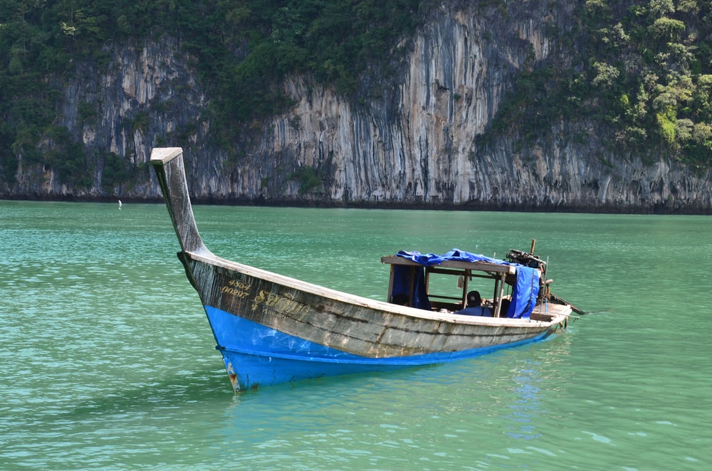 blue and brown boat on body of water during daytime