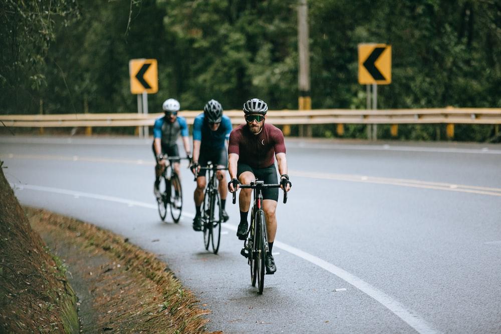 men riding bicycle on road during daytime