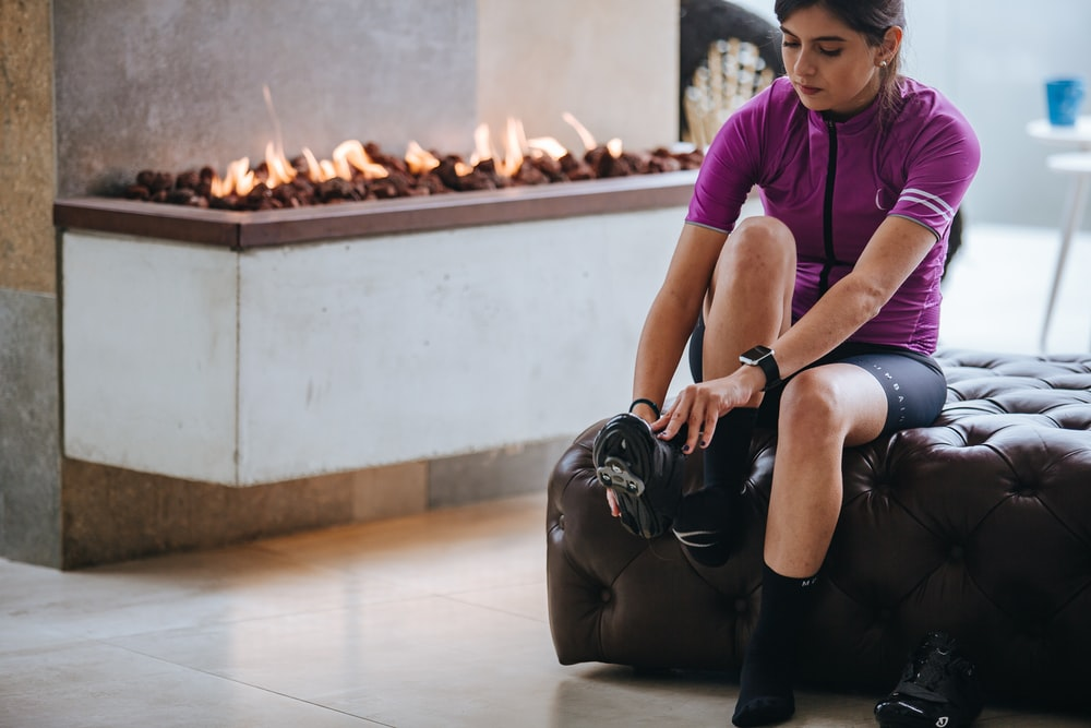 woman in purple crew neck t-shirt and black shorts sitting on white floor
