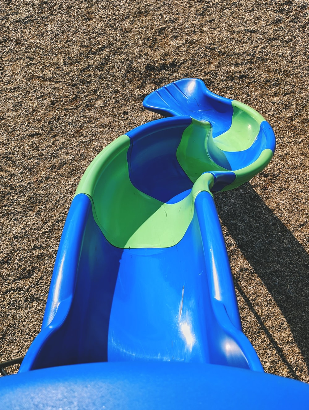 blue plastic slide on brown sand