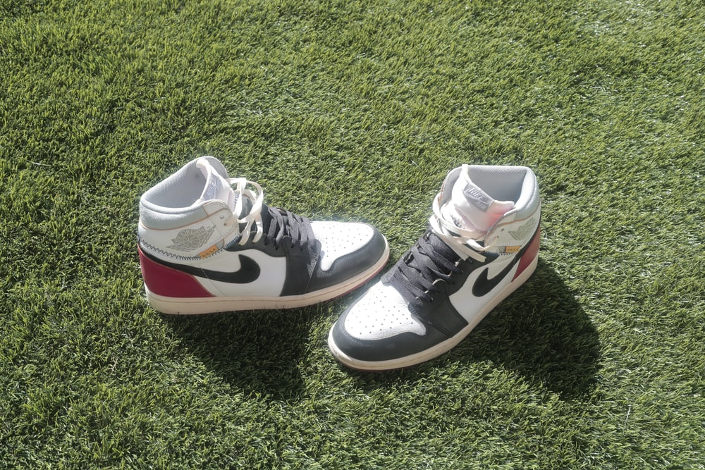 black and white nike high top sneakers on green grass