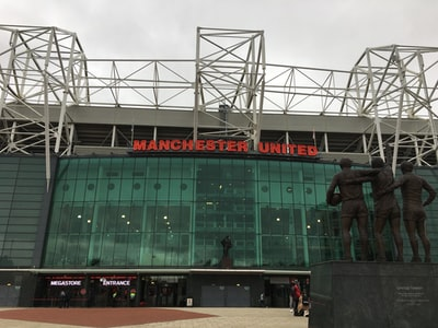 man in black jacket standing near green building during daytime manchester united zoom background