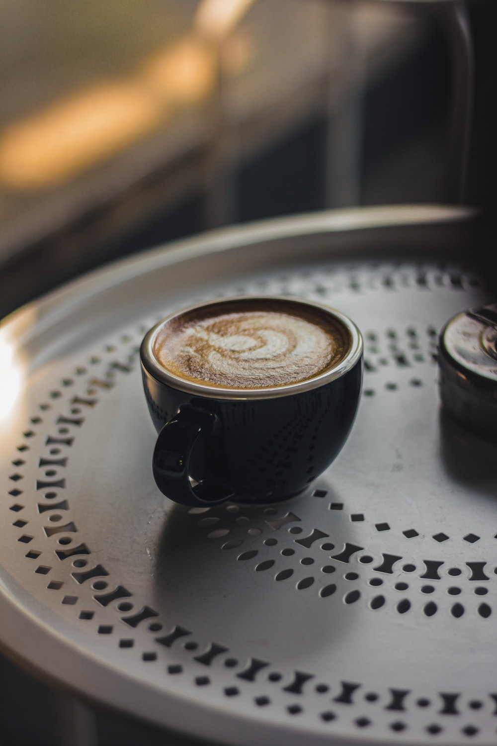 black ceramic cup with saucer on white table