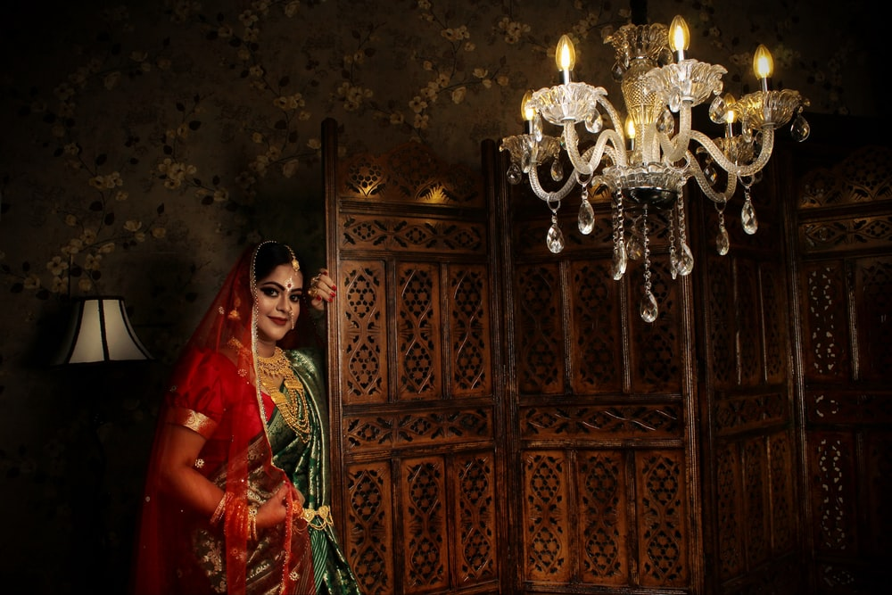 woman in red and green sari standing beside brown wooden door