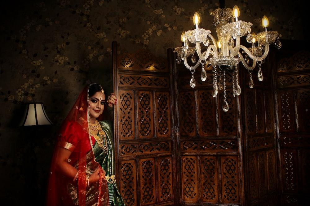 woman in red and green sari standing beside brown wooden door
