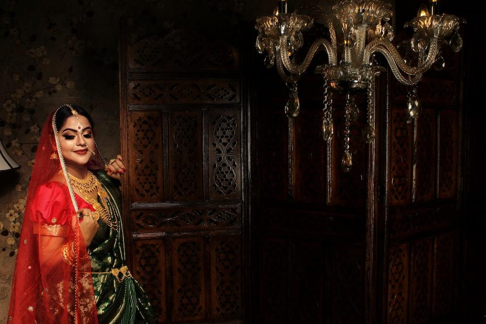 woman in red and green dress standing beside brown wooden door