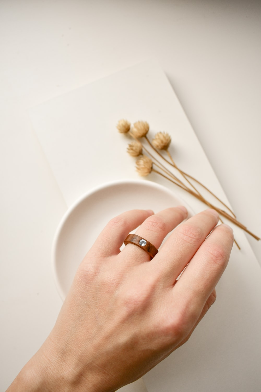 person wearing gold wedding band holding white ceramic plate