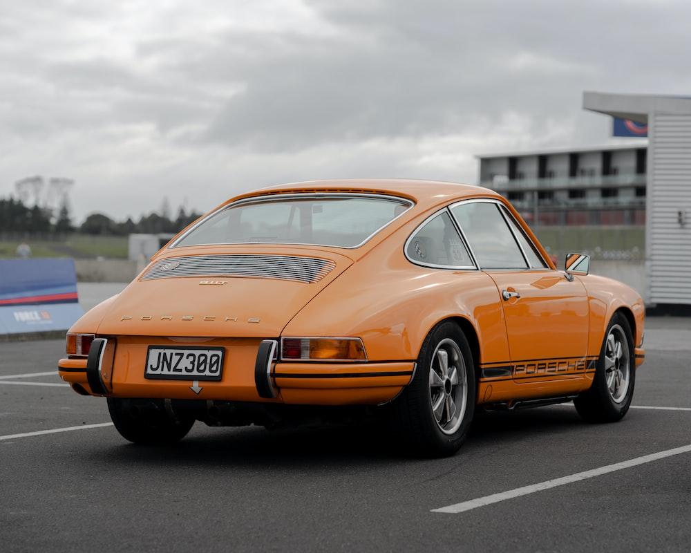 orange porsche 911 on road during daytime
