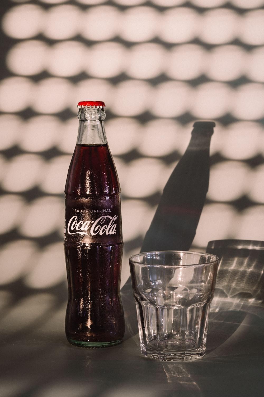 coca cola bottle beside drinking glass