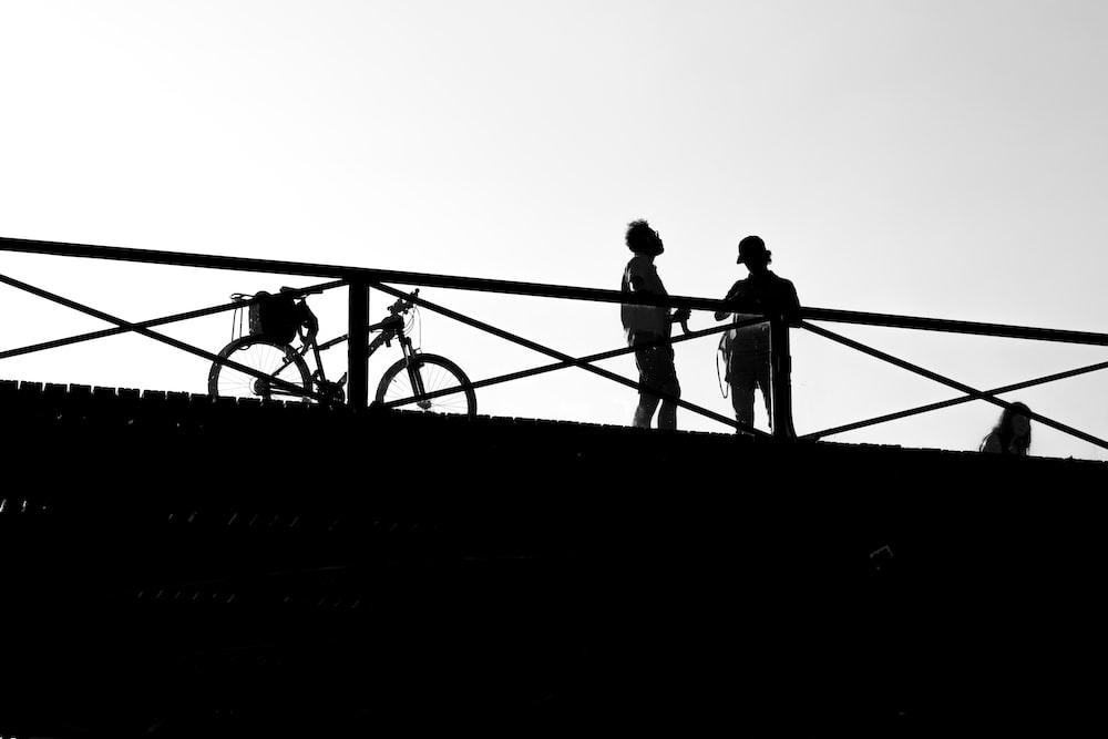 silhouette of 3 men standing on metal railings