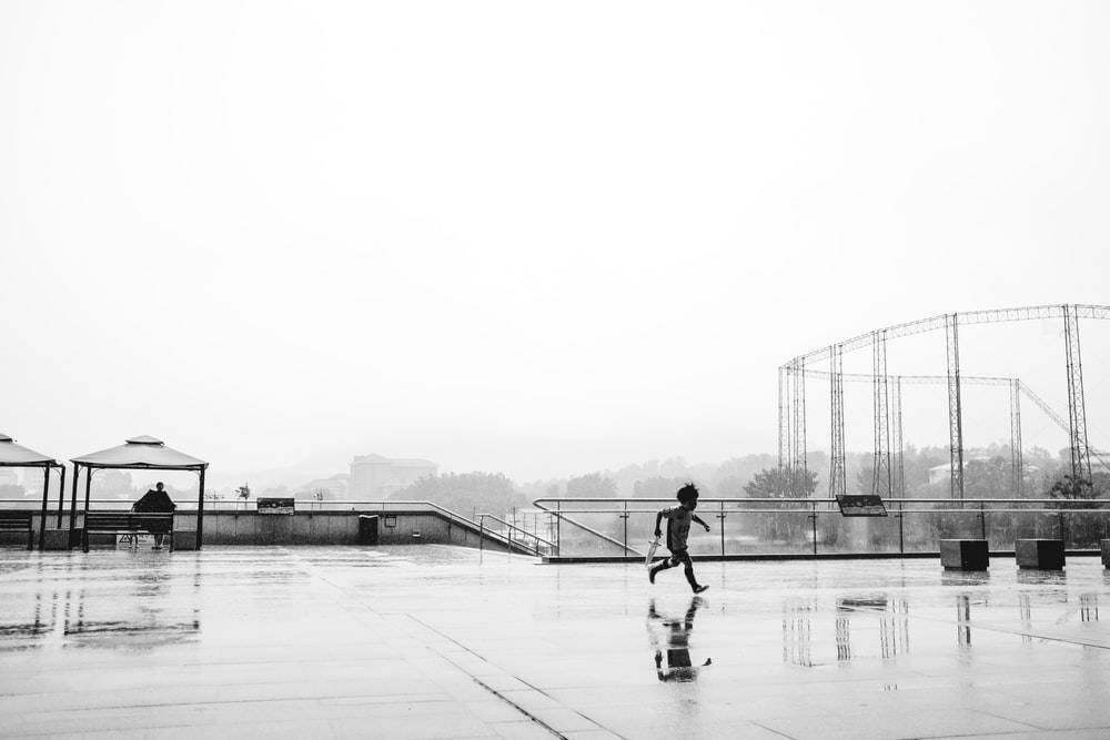 grayscale photo of girl running on wet floor