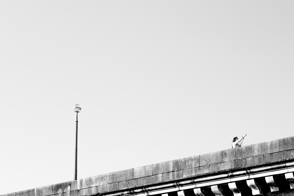 grayscale photo of man standing on top of building