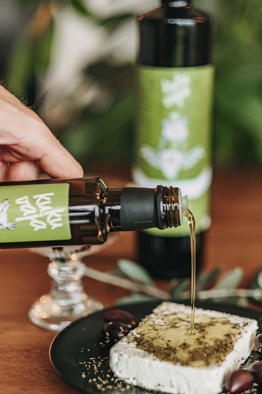 person pouring water on green and black bottle