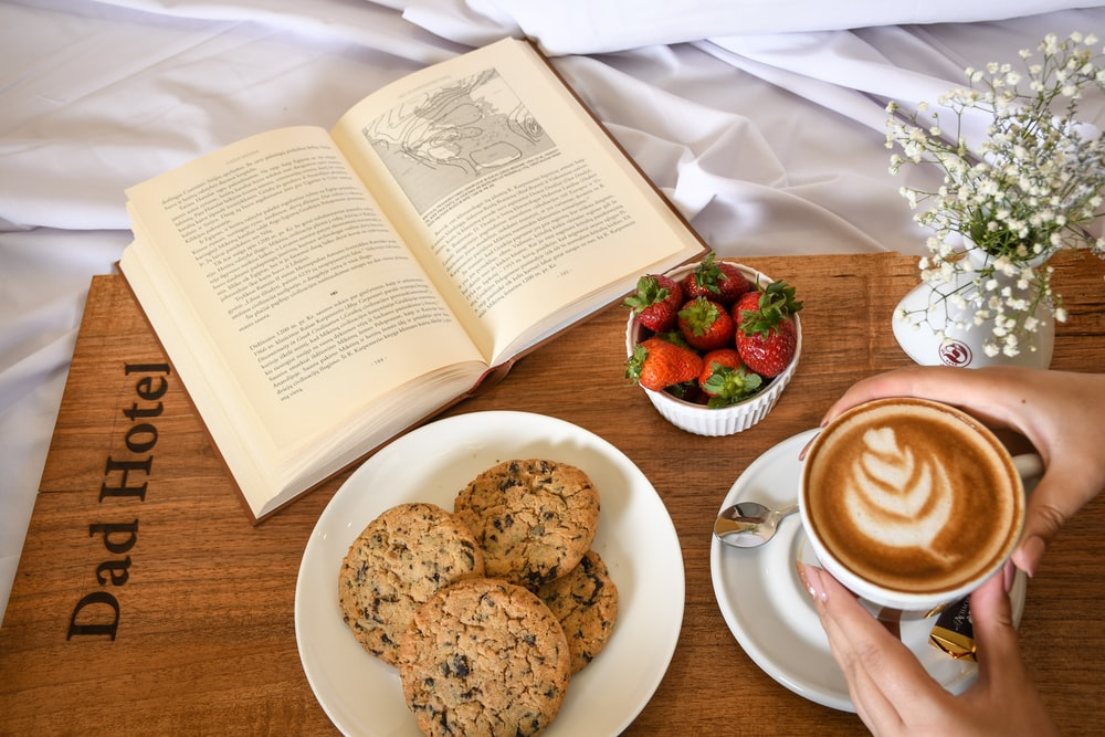 cookies on white ceramic plate beside white ceramic mug with saucer