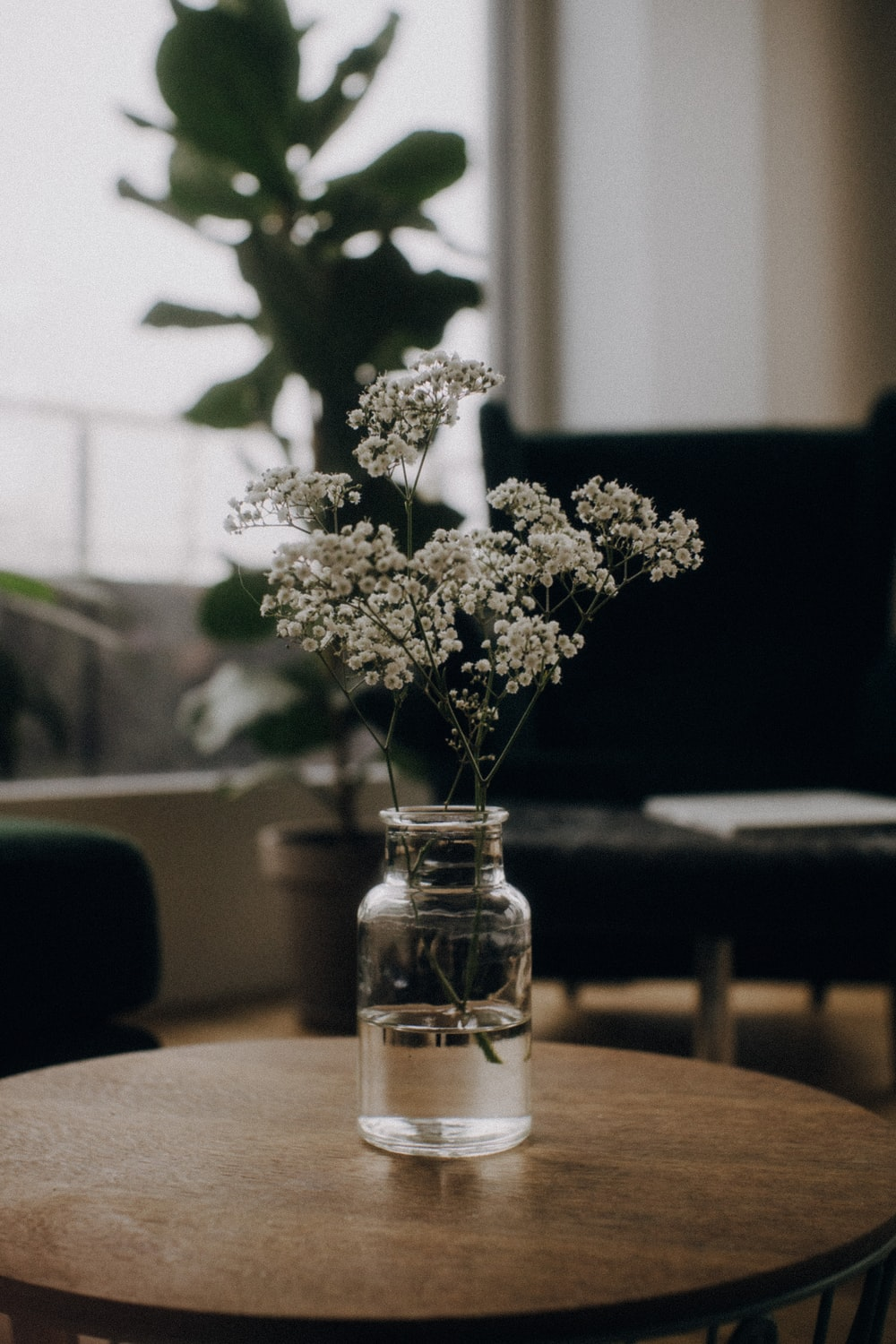 white flowers in clear glass jar on brown wooden table