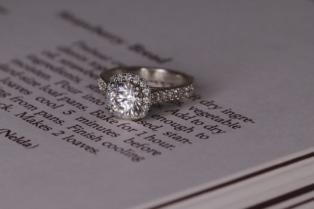 silver diamond ring on white book page