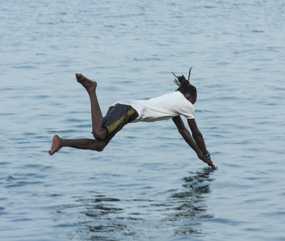 man in white t-shirt and yellow shorts jumping on water