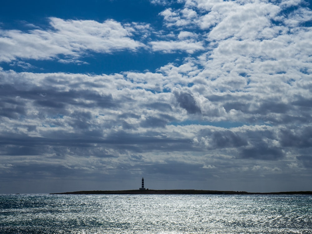 silhouette of person standing on sea under cloudy sky during daytime