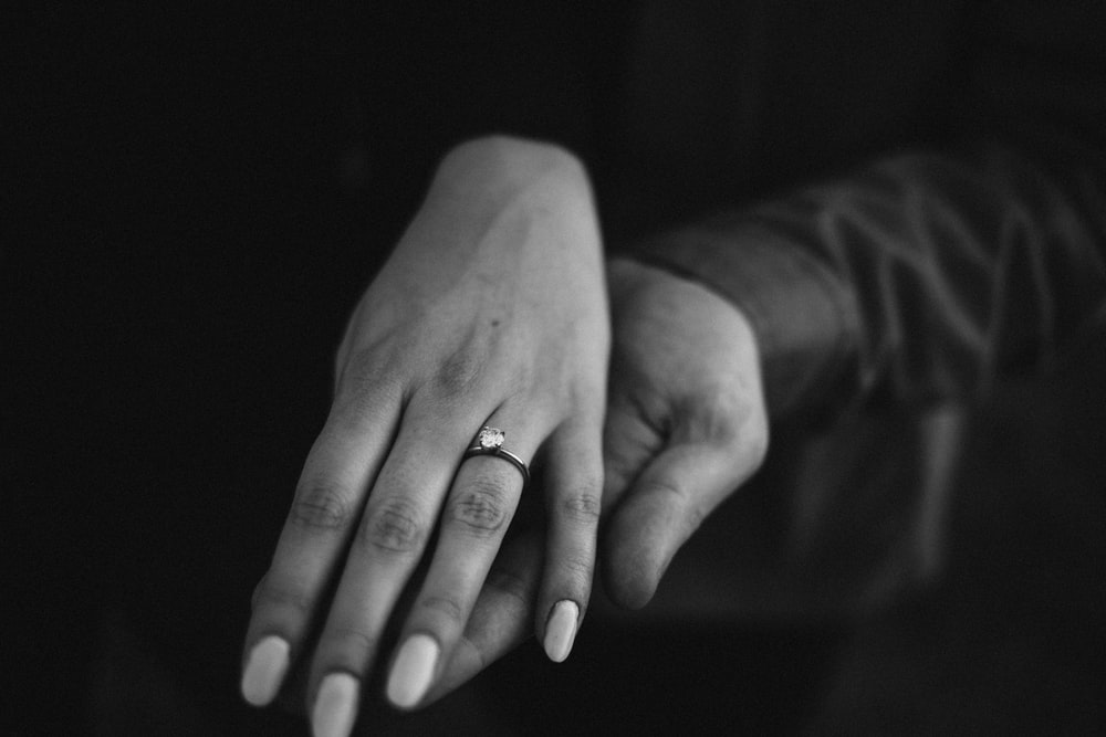 grayscale photo of person wearing ring