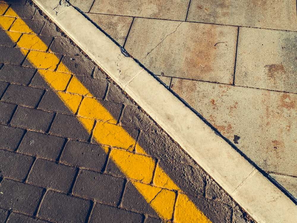 gray concrete pavement with yellow and white line