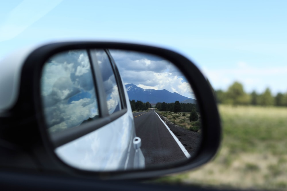 car side mirror showing road during daytime