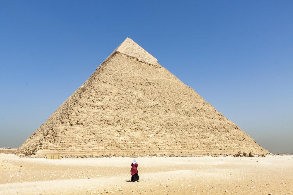 woman in black jacket walking on brown sand near pyramid under blue sky during daytime