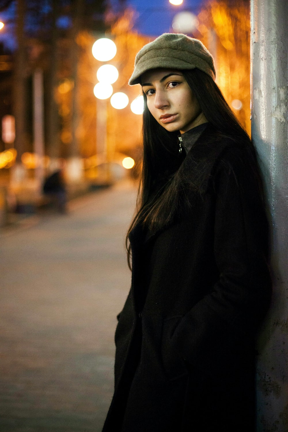 woman in black coat standing near the wall
