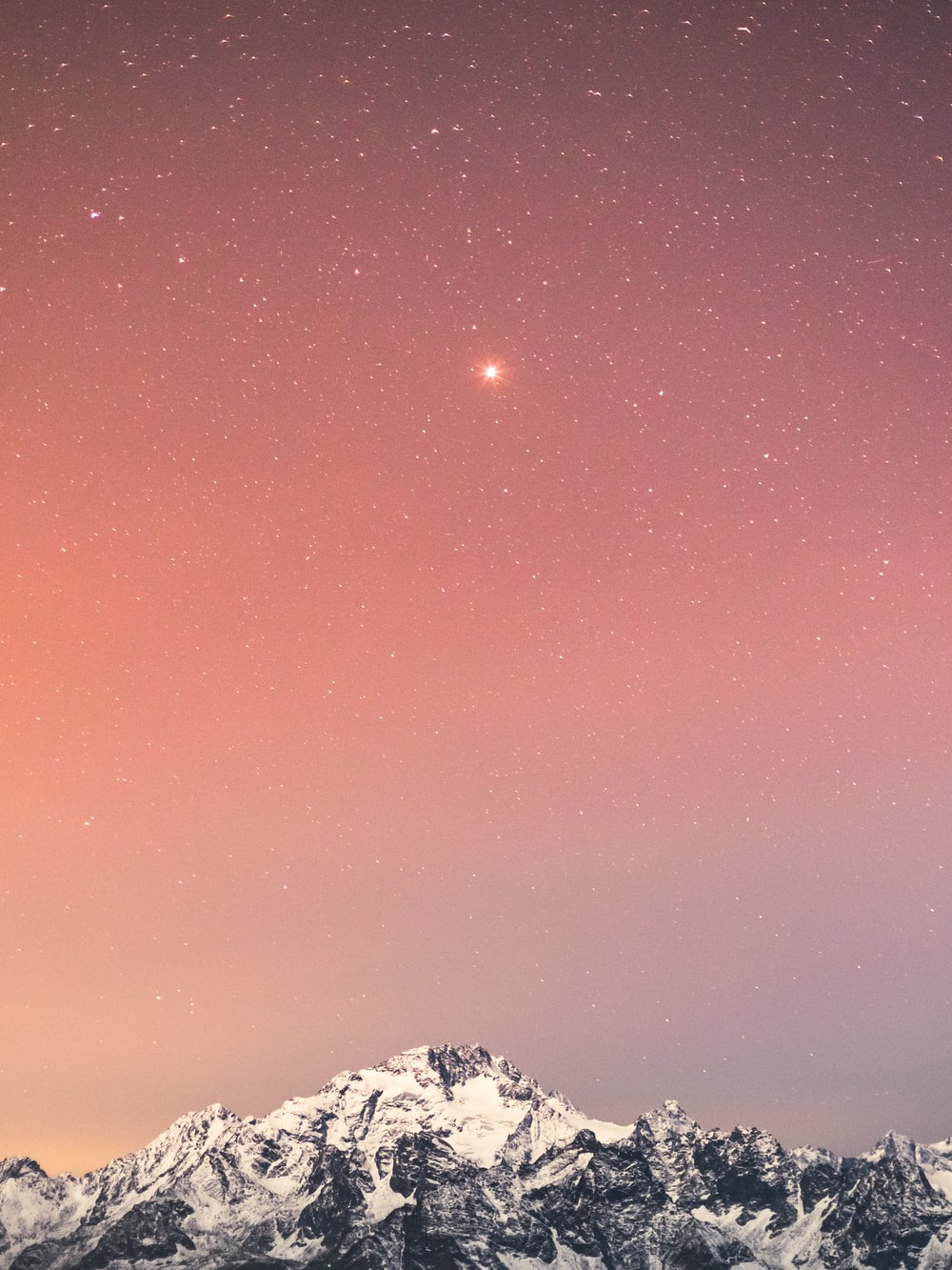 snow covered mountain under blue sky with stars during night time