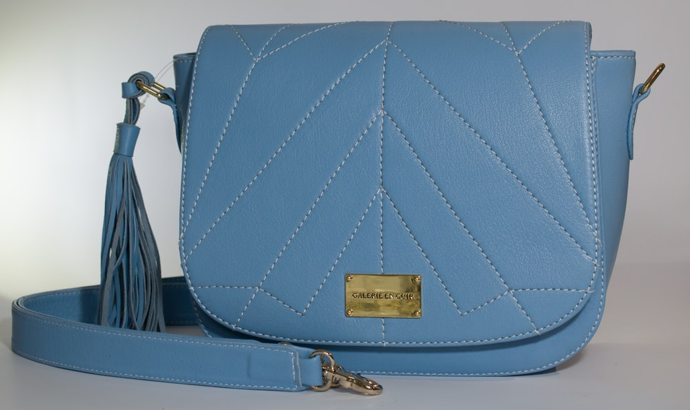 blue leather sling bag on white table
