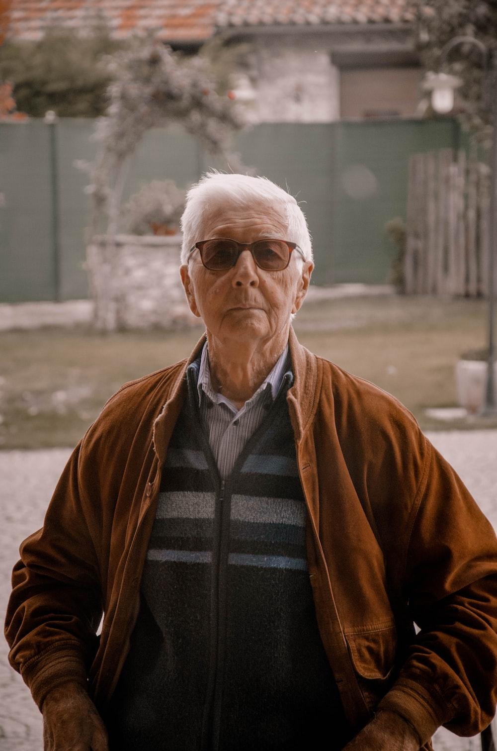 man in brown jacket wearing black framed eyeglasses