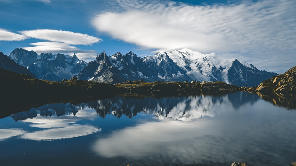 snow covered mountain near lake under cloudy sky during daytime