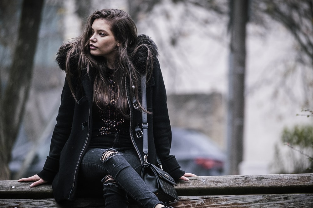 woman in black jacket and blue denim jeans sitting on brown wooden bench during daytime