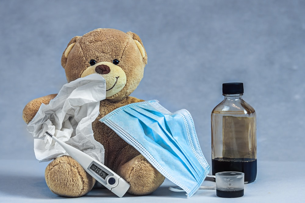 brown bear plush toy on blue textile
