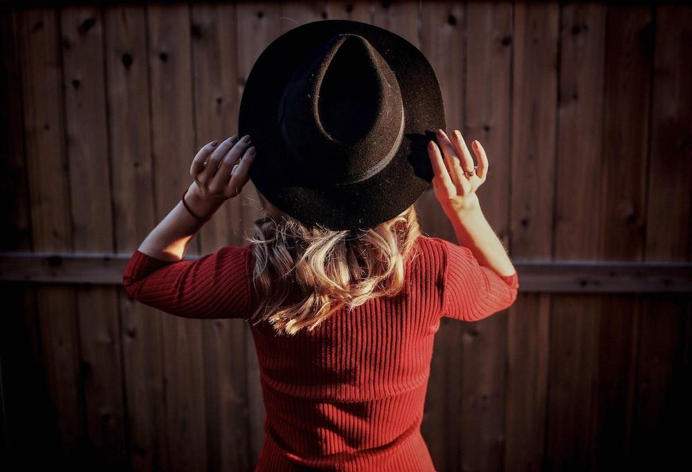 woman in red long sleeve shirt wearing black fedora hat