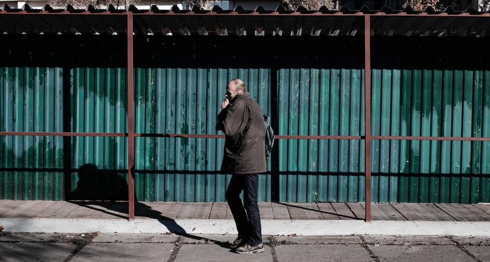 man in black jacket standing near green metal gate during daytime