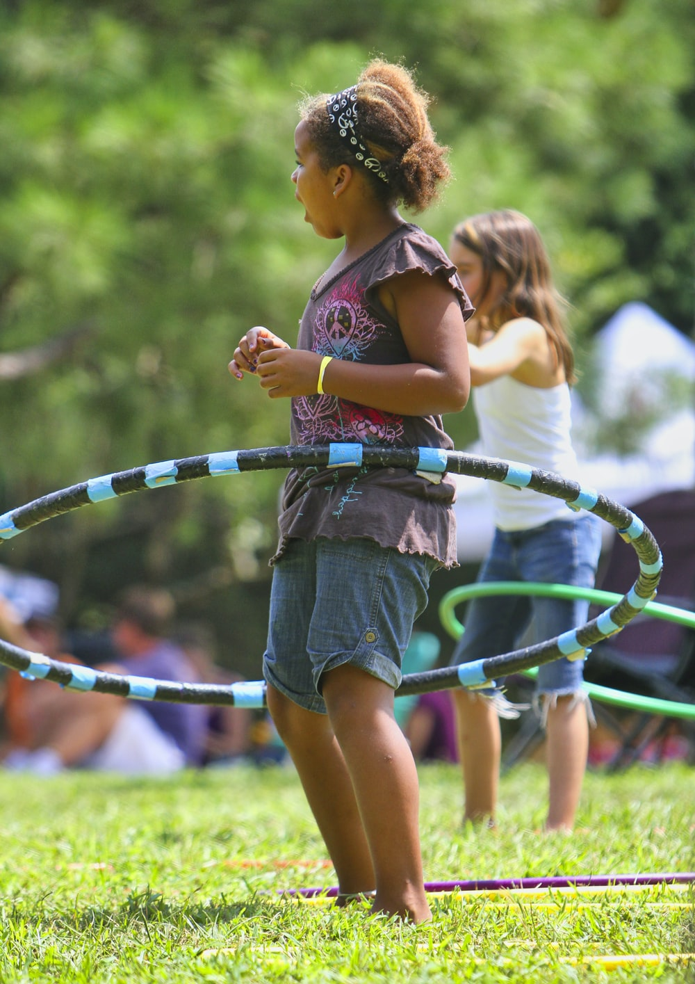 girl in blue denim shorts holding green and blue rope