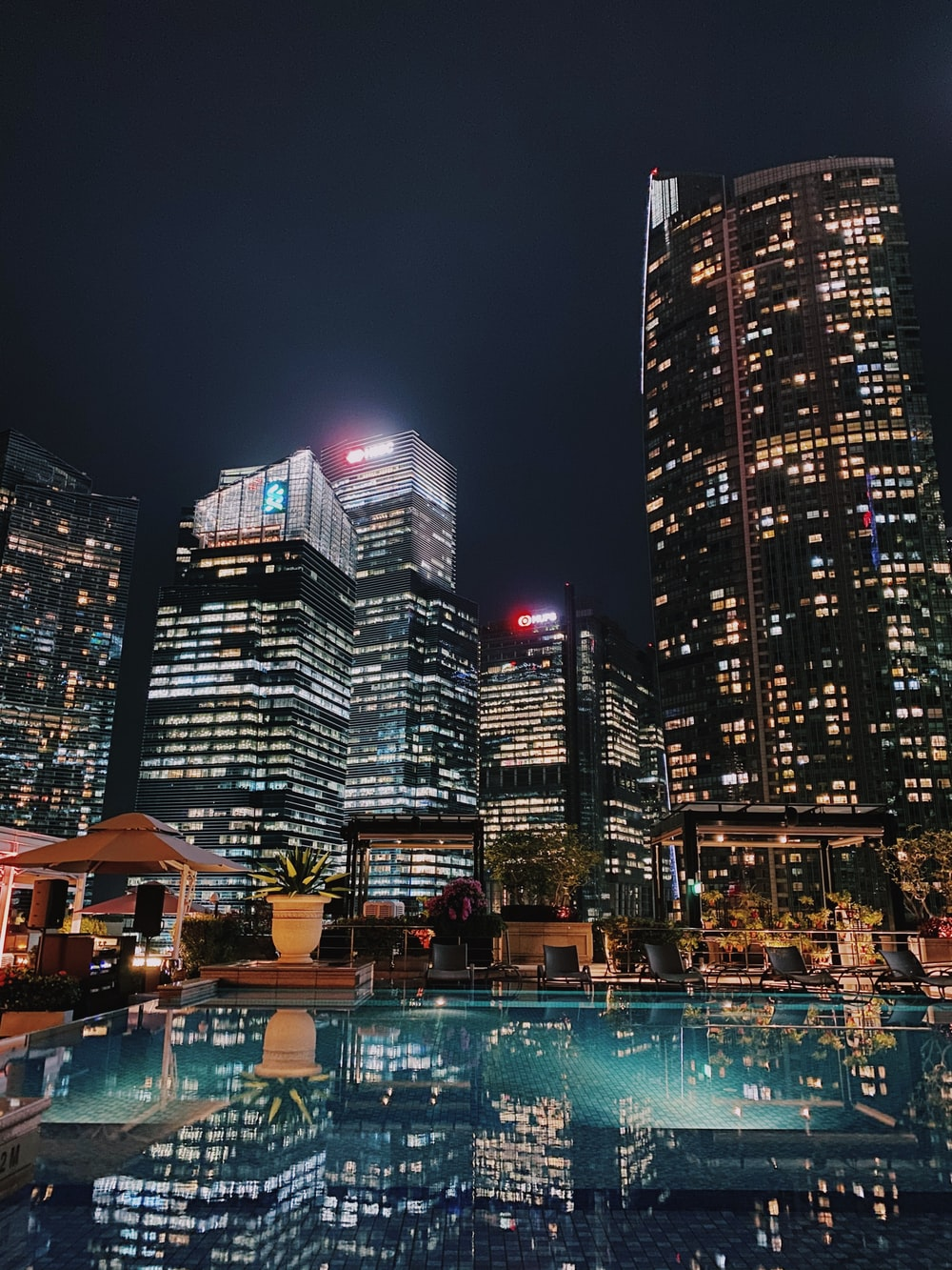 high rise buildings near body of water during night time
