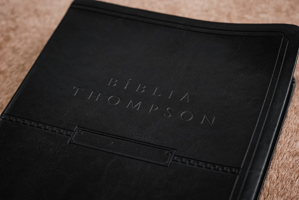 black leather book on brown wooden table