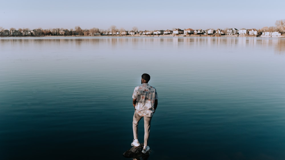 man in gray shirt standing on body of water during daytime