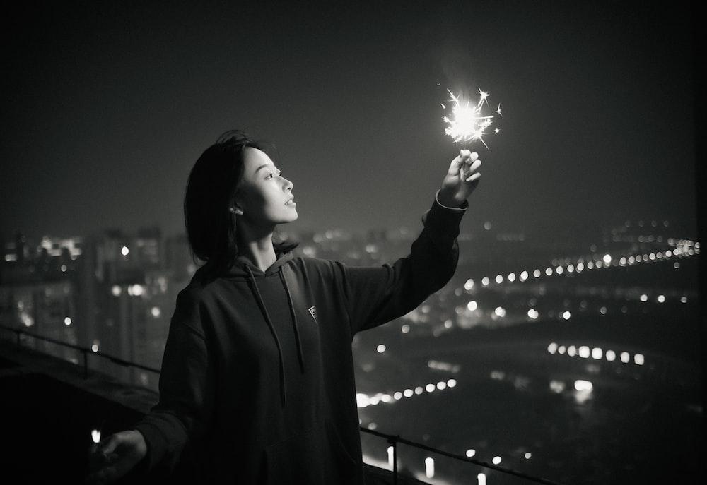 woman in gray coat holding sparkler