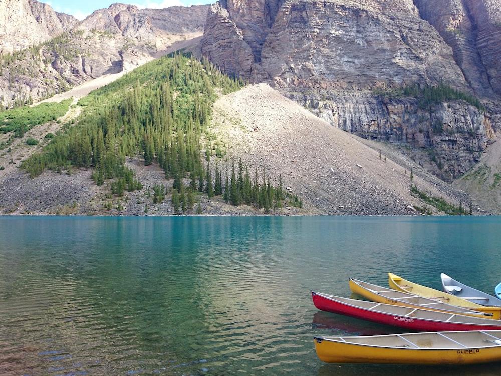 red and yellow kayak on lake near mountain during daytime
