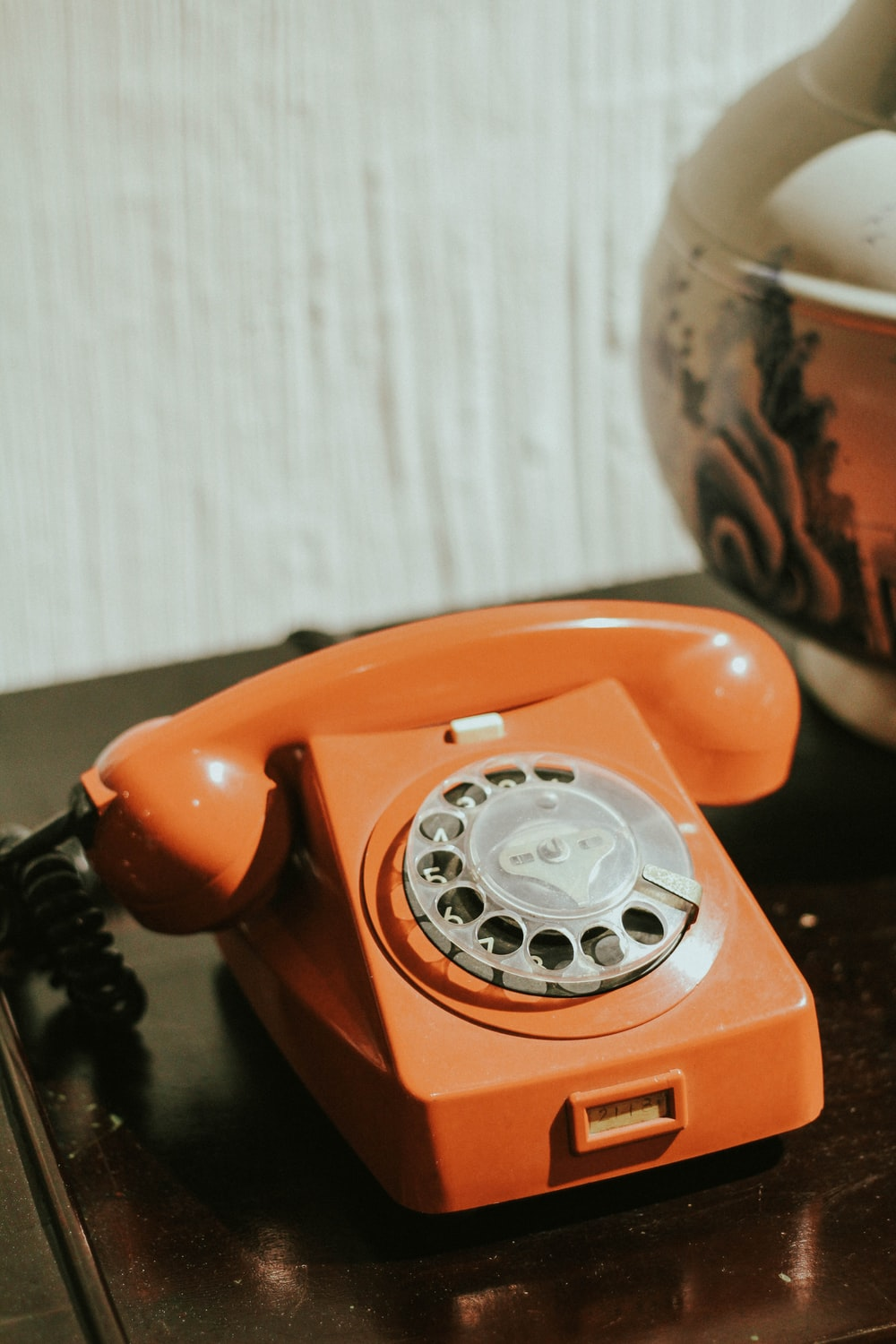 red rotary telephone on brown wooden table